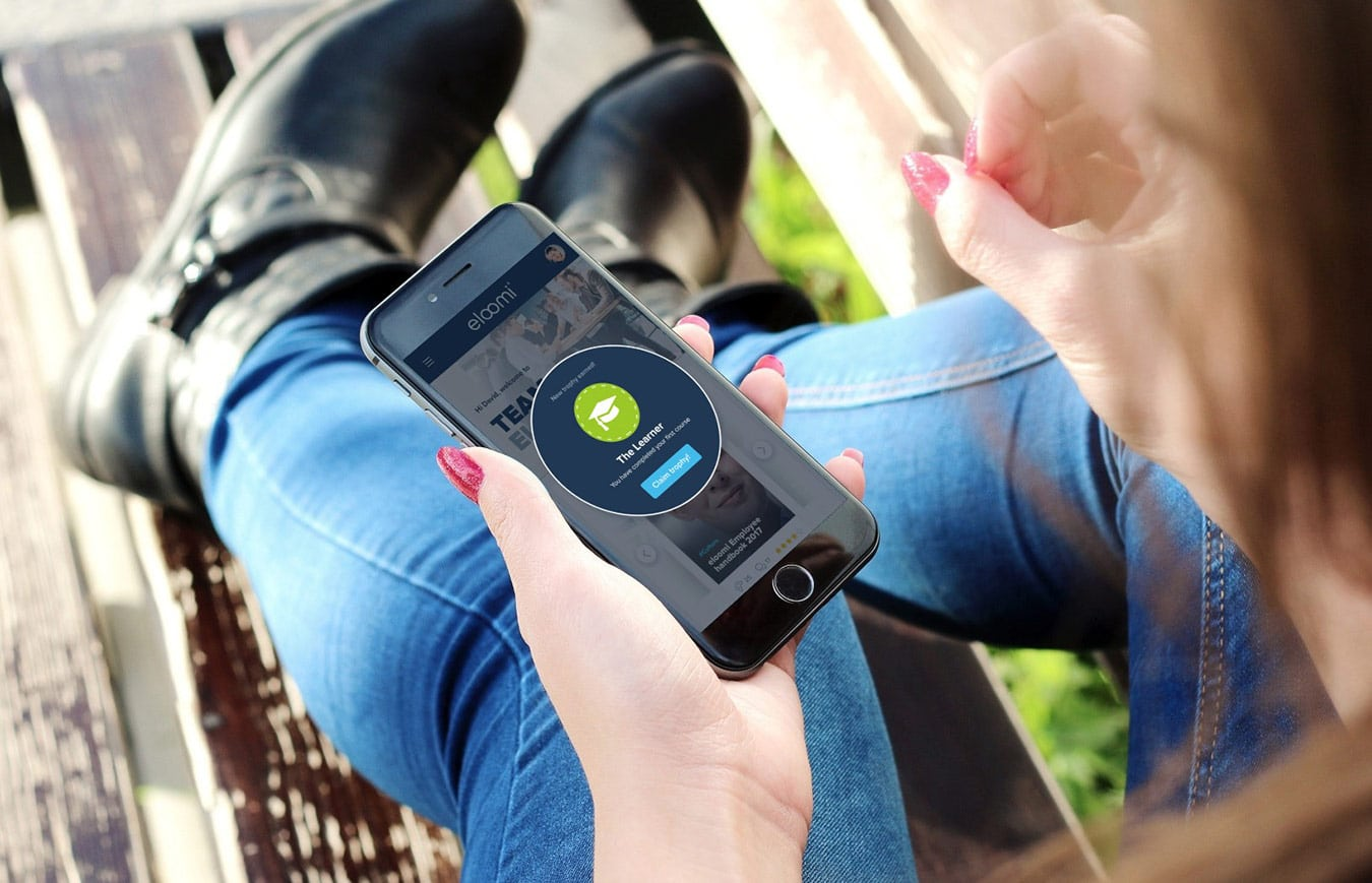 eloomi microlearning on mobile device, woman holding a mobile phone