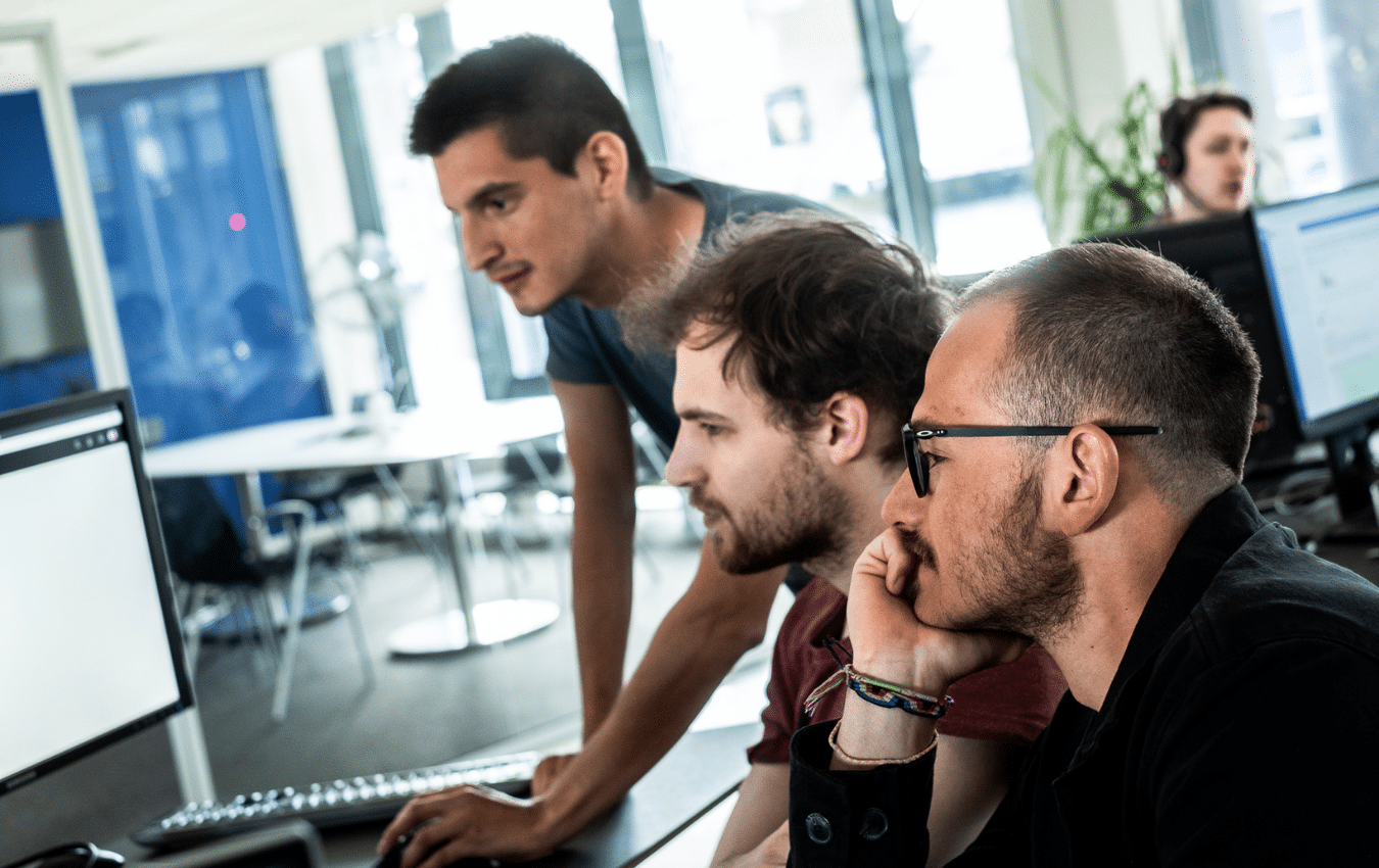 Three men at the office in front of a pc