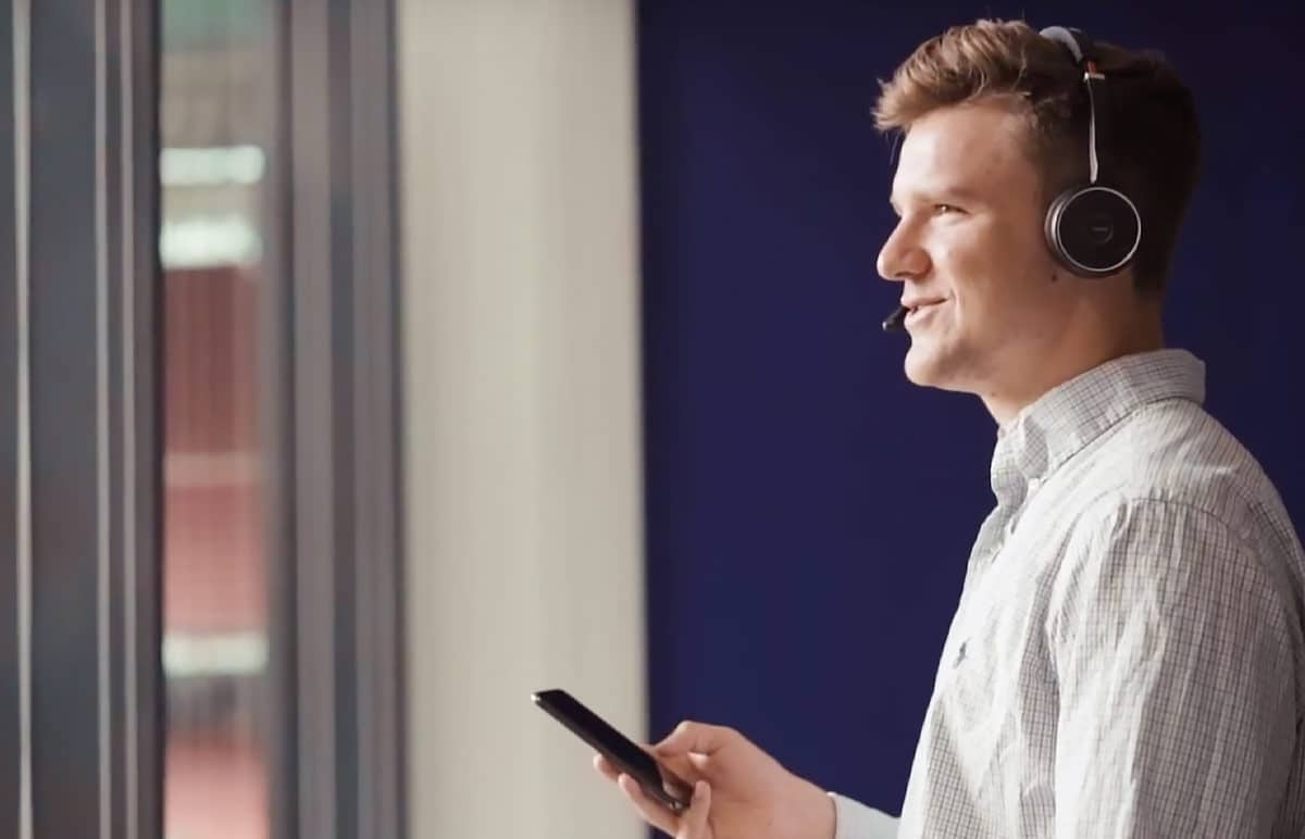 Jack standing with the phone by the window while talking to a customer in eloomi