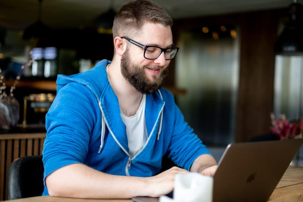 man in front of a laptop, working remotely