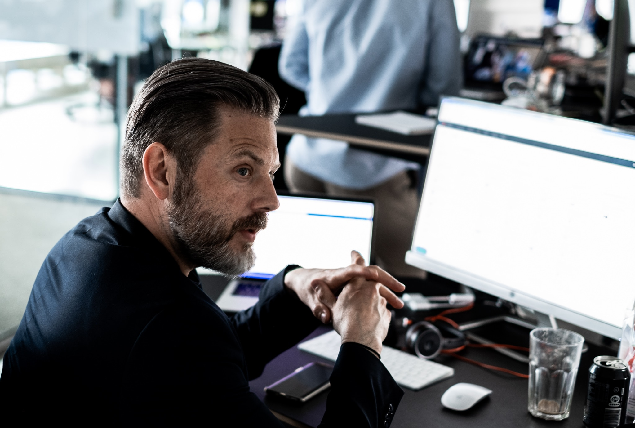male employee working in front of a screen in an open office space