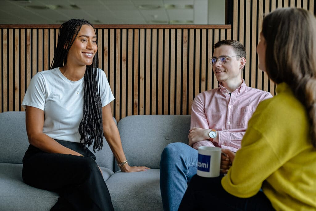 one man and two women smiling and talking in an office environment